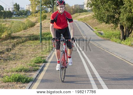 Sport and Cycling Ideas. Portrait of Professional Male Cyclist Doing Uphill Out of the Saddle on Road Bike. Fully Equipped in Professional Outfit. Horizontal Image