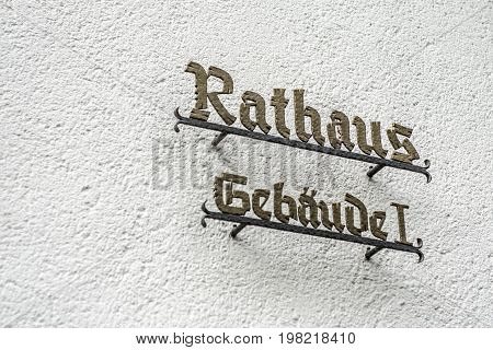 Wall with sign saying Rathaus Gebaeude 1 German town hall translation: town hall Building 1