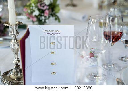 Dinner table set wine glas candle burning card Event detail - German header text hochzeitsmenu translation Wedding menu Copyspace to fill