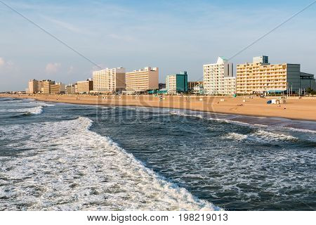 VIRGINIA BEACH, VIRGINIA - JULY 13, 2017:  High-rise hotels line the oceanfront boardwalk  as day breaks in this popular resort area.
