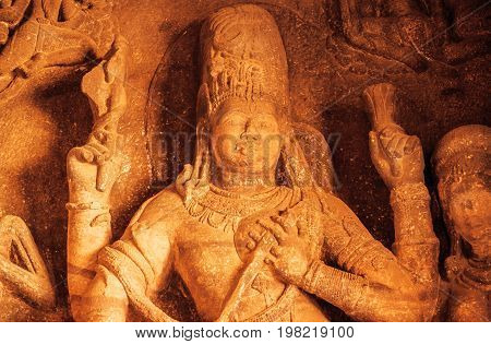 Face of Vishnu Lord in sculpture with many details on wall of old relief. Ancient Indian architecture of 6th century. Reliefs in Badami, India.