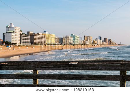 VIRGINIA BEACH, VIRGINIA - JULY 13, 2017:  Railing of the fishing pier with a view of the oceanfront hotels lining the boardwalk in the background of this popular summer tourist destination.