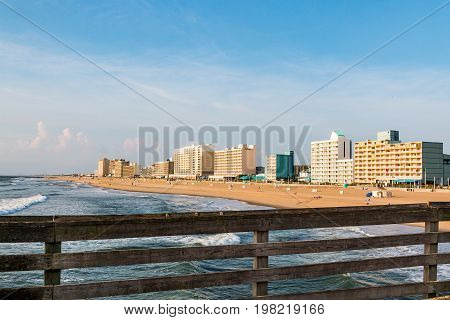VIRGINIA BEACH, VIRGINIA - JULY 13, 2017:  Railing of the fishing pier with a view of the oceanfront hotels on the south end of the 3-mile long boardwalk at this popular tourist destination.