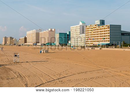 VIRGINIA BEACH, VIRGINIA - JULY 13, 2017:  The beach lies empty at daybreak at this popular oceanfront tourist destination with a 3-mile long boardwalk lined with high-rise hotels.