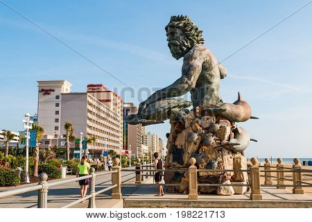 VIRGINIA BEACH, VIRGINIA - JULY 13, 2017:  The King Neptune statue by sculptor Paul DiPasquale along the oceanfront boardwalk lined with high-rise hotels at this popular tourist destination.