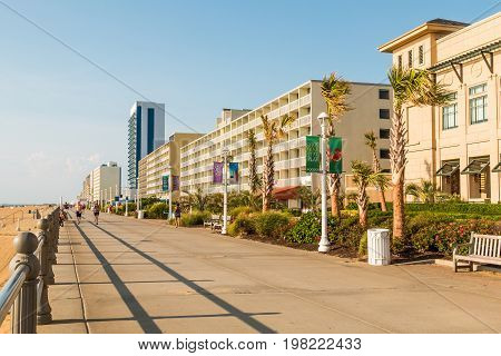 VIRGINIA BEACH, VIRGINIA - JULY 13, 2017:  The nearly empty boardwalk at daybreak along the oceanfront of this popular tourist destination, lined with high-rise hotels and stretching for 3 miles.