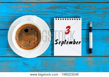 September 3rd. Day 3 of month, loose-leaf calendar and morning yellow cup with coffee or latte, student workplace background. Autumn time.