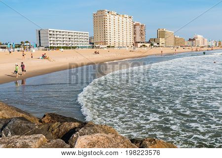 VIRGINIA BEACH, VIRGINIA - JULY 13, 2017:  View of boardwalk hotels and people enjoying the beach as seen from the oceanfront jetty.