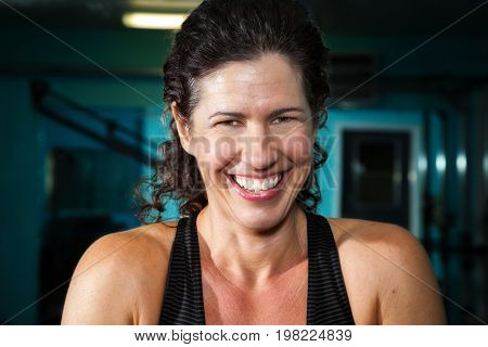 Close up portrait of a woman laughing for the camera. She has a big smile and curly black hair.