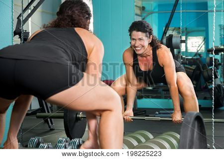 A happy female weight lifter looks in the mirror with a big smile as she prepares for a dead lift.