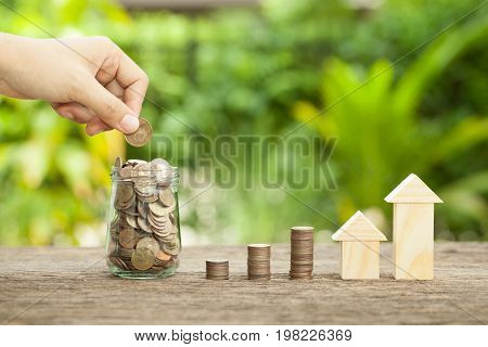 Hand's women putting golden coins in money jar. Concept of real estate investments Home insurance Savings plans for housing. The concept of financial savings to buy a house.