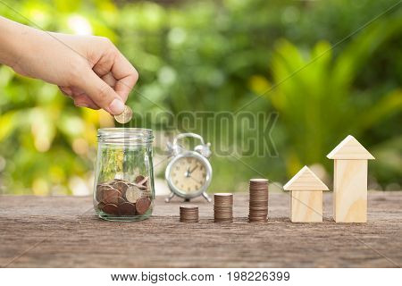 Hand's women putting golden coins in money jar. Concept of real estate investments Home insurance Savings plans for housingTime to save The concept of financial savings to buy a house.