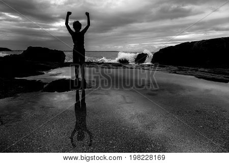 Silhouette Of A Boy With Raised Arms Over Sunset Background. Freedom And Success Feeling. Black And