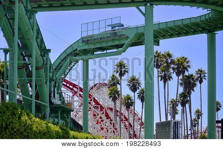 A water splash ride and roller coaster with palm trees at a seaside amusement park