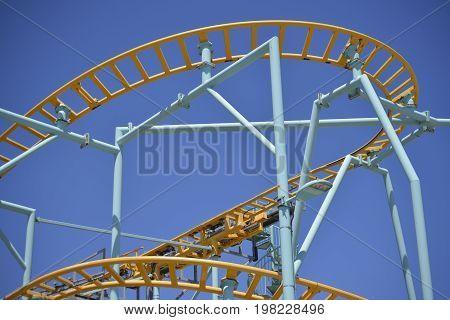 A mini rollercoaster track against a blue sky