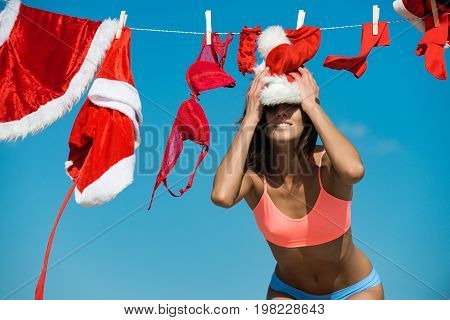 Laundry and dry cleaning. Santa claus girl hanging clothes for drying. Christmas woman with happy face outdoor. Xmas red costume on rope with pin. New year girl on sunny blue sky.