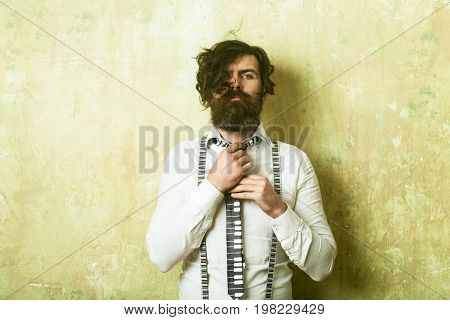 Hipster in shirt and suspenders with musical tie. Guy or businessman at textured wall. Business fashion and beauty. Fashion model with stylish hair. Man with long beard and mustache on face.