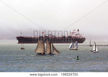 A large crude oil tanker sailing alongside several sailboats and a larger schooner in fog.