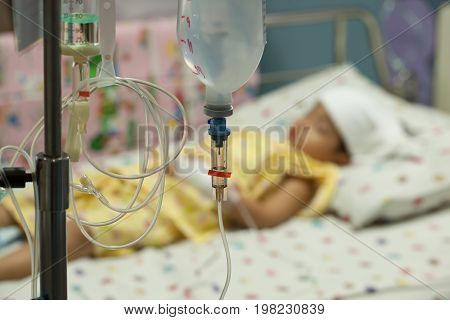 Close up saline IV drip for patient and Infusion pump in hospital In the hospital with a fragment of medical equipment and patients boy High fever for bacterial infections.