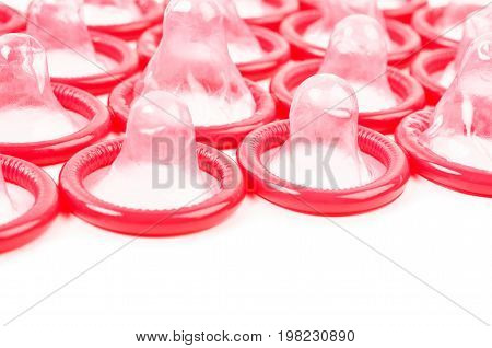 Red condom with open pack on white background.