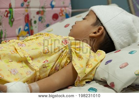 a little Boy attaching intravenous tube to patient's hand in hospital bed thermometer boy hospitalized patients towel to hi fever