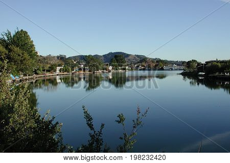 A quiet lagoon with homes on all sides and lots of trees, all reflected in the water.