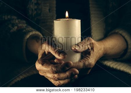 Candle in the hands of an elderly woman close-up.