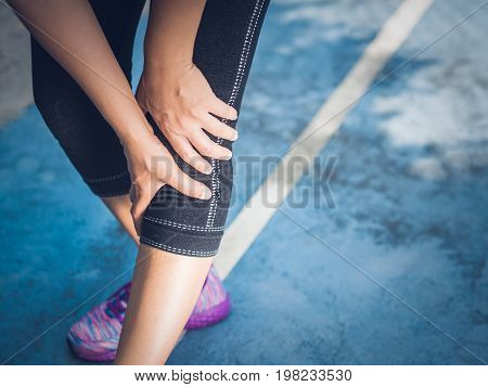 Closeup runner sport knee injury. Woman in pain while running. Sport injuries concept.