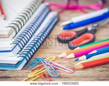Colorful school supplies with books color pencils pink glasses pen cutter and clips on wooden background. Back to school concept.