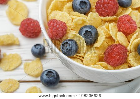 Cornflakes With Fresh Berries Raspberry And Blueberry In White Bowl On The Table. Healthy Breakfast.
