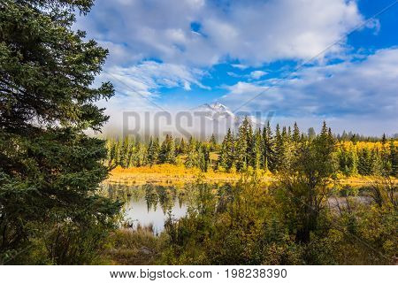 Patricia Lake among the pines. Pyramid Mountain among fog and clouds. Rocky Mountains in Canada. The concept of ecotourism