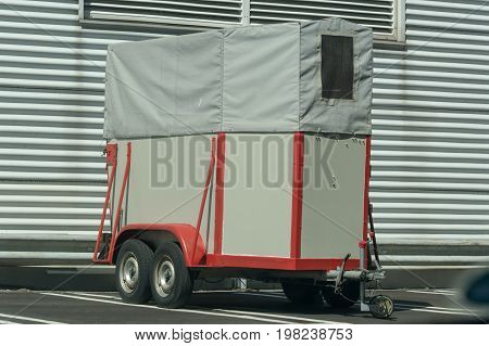 Old horse transport trailer in front of a metal wall.