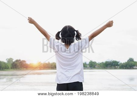 gril with arms outstretched. Freedom and happiness with sunset at park