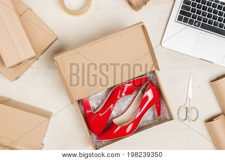 Stylish woman's shoes in a box on wooden table.