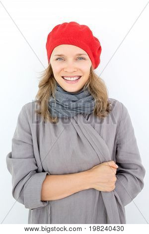 Cheerful beautiful young French woman wrapping up on cooler day in cozy cardigan. Jolly girl wearing red beret looking at camera opposite white background. Cold concept
