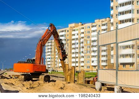 Crawler Excavator to hammer a steel piles into ground. Construction of high-speed bypass road around Krasnoe Selo Saint Petersburg. Heavy machine equipment for excavation works in industry. Russia