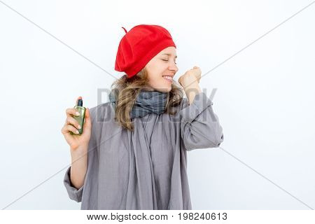 Excited young woman testing new perfume. Pleased happy French woman in red beret smelling wrist and enjoying new fragrance of perfume. Aroma concept
