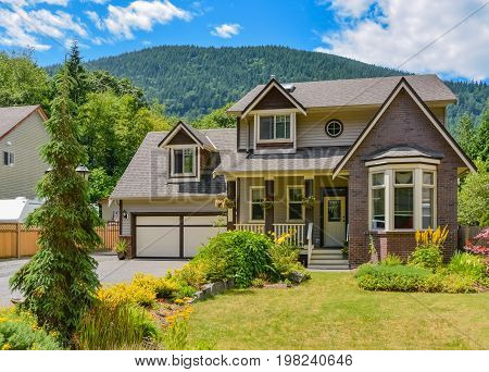 Big family house with wide garage and decorated front yard on mounting and blue sky backgrould