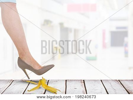Digital composite of Woman stepping on banana peel about to slip mistake