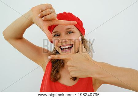 Happy talented young female photographer choosing place for shot. Portrait of French woman in red clothes holding hands in shape of frame and smiling at camera. Creative view concept