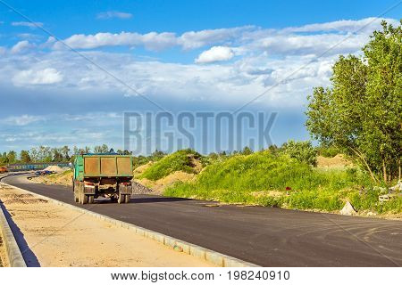 Heavy truck on construction of high-speed bypass road around Krasnoe Selo Saint Petersburg. Heavy machine equipment for civil industrial construction. Russia