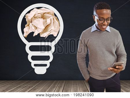 Digital composite of Man on phone standing next to light bulb with crumpled paper ball in front of blackboard