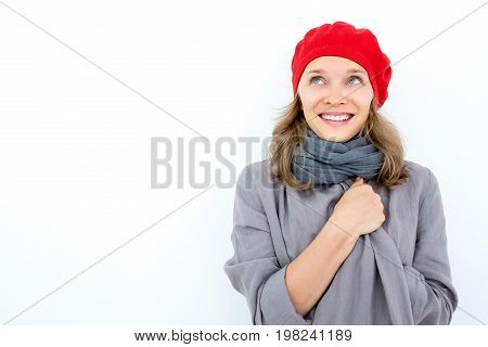 Smiling young woman dreaming of good weather. Pensive attractive French girl in red beret wrapping up in warm cardigan and looking up. Thoughts concept