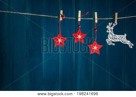 Christmas background. Reindeer and red christmas stars on clothespin on deep blue wooden background with copy space. Christmas or New Year card template.