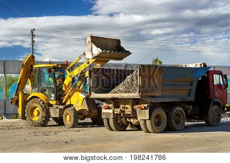 Heavy Tractor loads truck with rubble using bucket. Construction of high-speed bypass road around Krasnoe Selo Saint Petersburg. Heavy industrial machinery equipment for excavation works. Russia