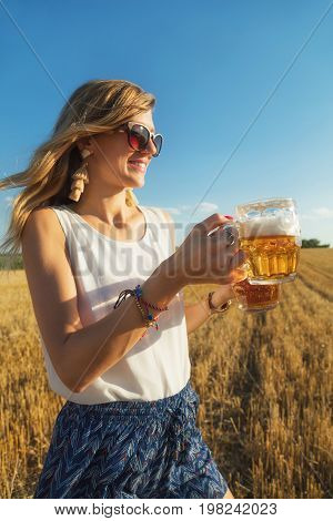 Happy girl holding beer glasses in a big wheat-field. Optical focus is on the hand and glass.