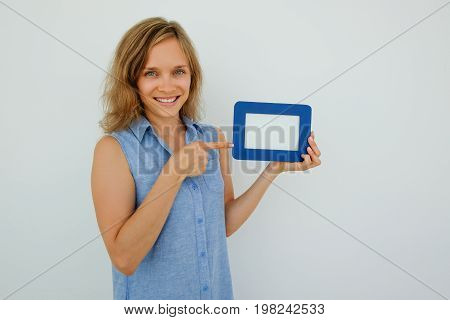 Closeup portrait of smiling young attractive woman looking at camera, holding empty picture frame and pointing at it. Isolated view on grey background.