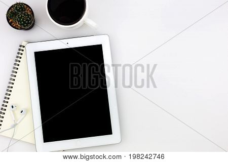 Modern white office desk top table with tablet a cup of coffee notebook and other supplies. Top view with copy space on white background. Top view flat lay.
