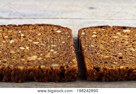 Slices of whole grain brown bread on wooden table.