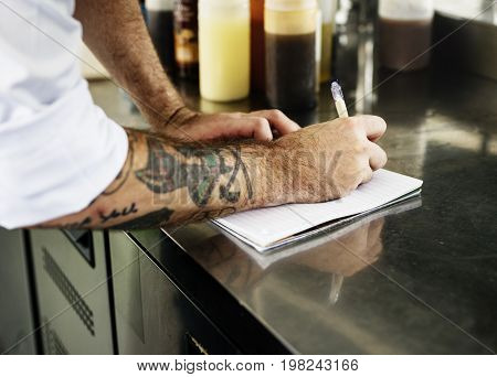 Hand with tattoo writing down an inventory in the kitchen